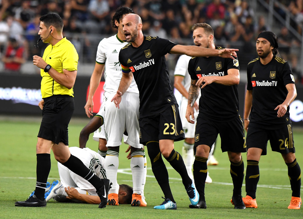 Los Angeles FC defender Laurent Ciman (23) yells toward a official after Portland Timbers midfielder Sebastian Blanco grabs his ankle after being upended by upended by Los Angeles FC defender Jordan Harvey in the first half of a Major league Soccer U.S. Open Cup quarterfinals match at the Banc of California Stadium on Wednesday, July 18, 2018 in Los Angeles
