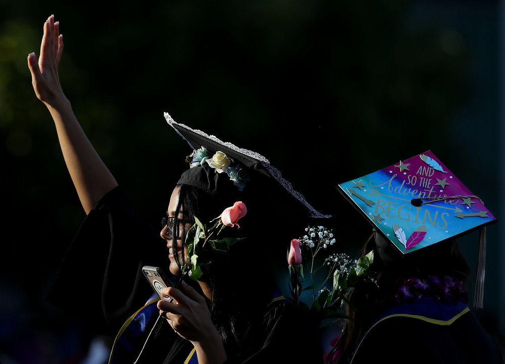 UCR graduates wave to as they find their families in the crowd during UC Riverside's School of Business graduation ceremony for Master and bachelor degree candidates on Pierce Lawn at UCR campus Friday in Riverside, Calif. June 15, 2018.