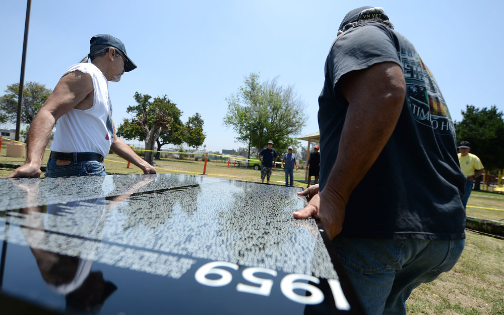Volunteers carry the first panel for installation of the Vietnam Moving Wall Thursday at Ayala Park in Bloomington. Volunteers, many being Vietnam veterans, helped construct the Vietnam Moving Wall in Ayala Park in Bloomington Thursday June 7, 2018. The wall, containing 58,318 names, with 132 being from San Bernardino County, will be on display 24-hours a day beginning Friday and lasting through Monday.