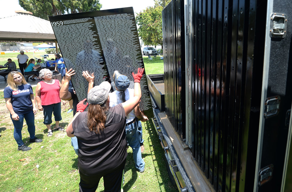 Volunteers pull the first panel of the Vietnam Moving Wall from its traveling crate Thursday at Ayala Park in Bloomington. Volunteers, many being Vietnam veterans, helped construct the Vietnam Moving Wall in Ayala Park in Bloomington Thursday June 7, 2018. The wall, containing 58,318 names, with 132 being from San Bernardino County, will be on display 24-hours a day beginning Friday and lasting through Monday.