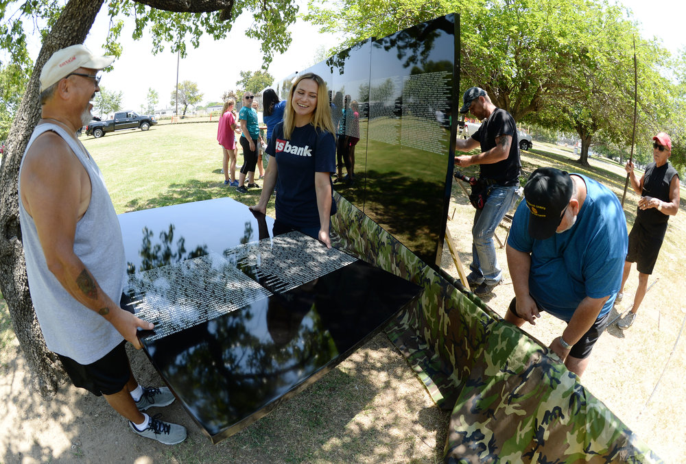 Volunteers carry one of the 70 Vietnam Moving Wall panels that were installed Thursday at Ayala Park in Bloomington. Volunteers, many being Vietnam veterans, helped construct the Vietnam Moving Wall in Ayala Park in Bloomington Thursday June 7, 2018. The wall, containing 58,318 names, with 132 being from San Bernardino County, will be on display 24-hours a day beginning Friday and lasting through Monday.