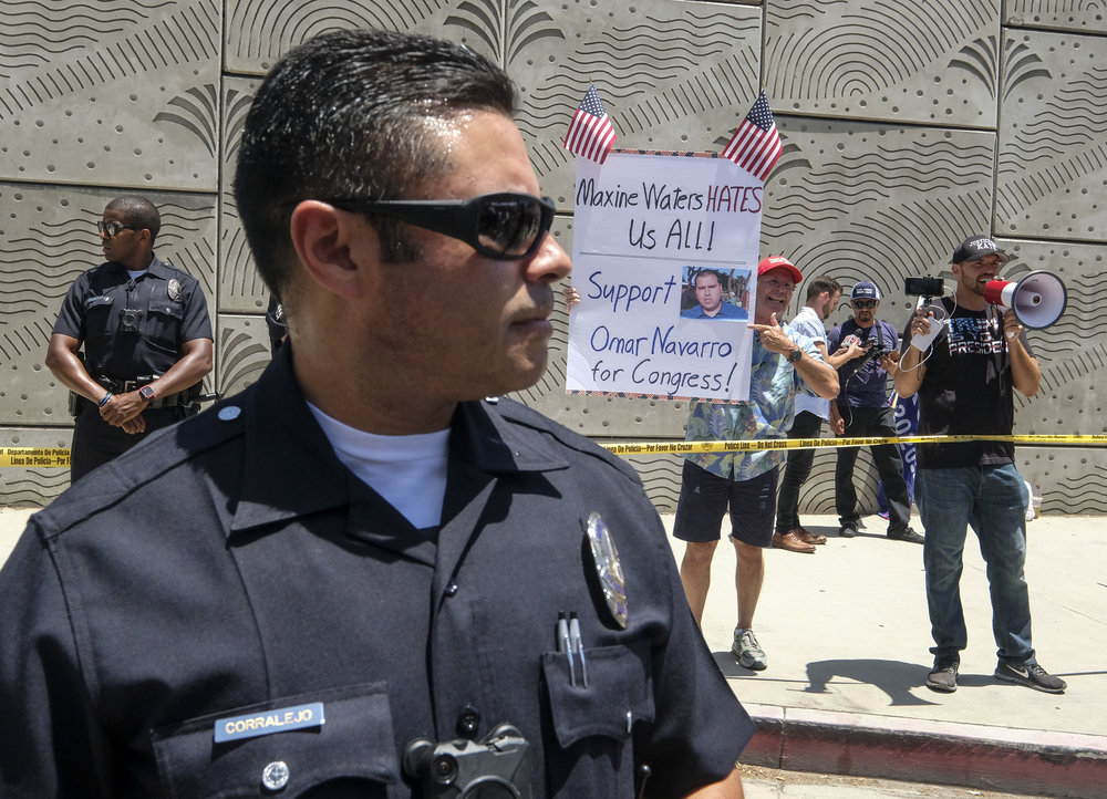 A police officer separates the Trump supporters, in the back, and the anti-Trump demonstrators during a march against the separation of immigrant families, in Los Angeles on June 30, 2018. It's one of 600-plus marches to be held across the country to demand an end to separating and detaining families, and organizers are urging attendees to wear white in a show of unity.