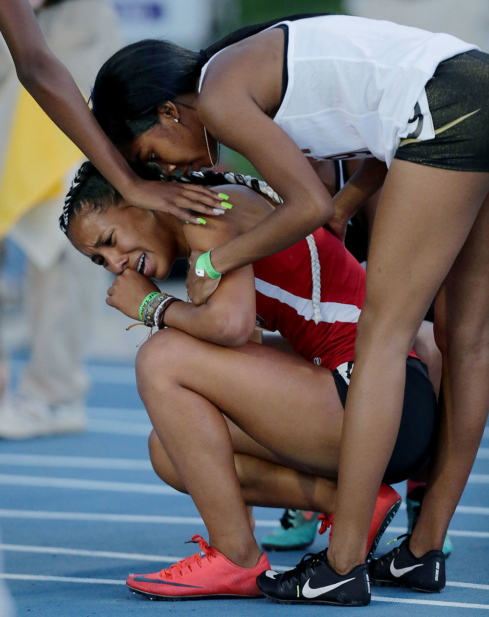 Segerstrom�s Nyree Brown is comforted by fellow runners after crashing into a hurdle and falling during the 100th annal CIF State Track and Field Championships at Buchanan High Saturday in Clovis, Calif. June 2, 2018.
