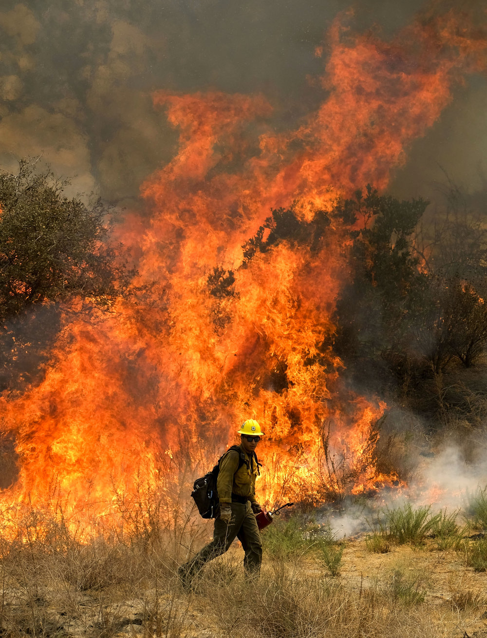 A firefighter battles the Holy Fire burning in the Cleveland National Forest in Lake Elsinore, California on Friday, Aug. 10, 2018.