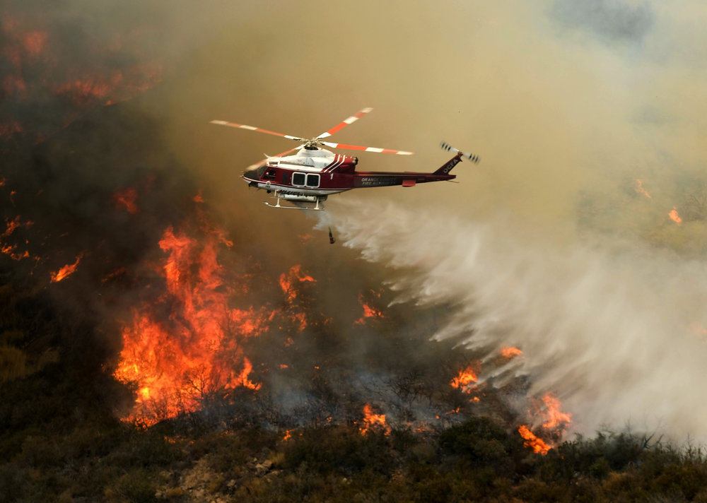 A helicopter drops water to a brush fire at the Holy Fire in Lake Elsinore, California, southeast of Los Angeles, on August 11, 2018. The fire has burned 21,473 acres and was 29 percent contained as of 8:30 a.m. Saturday, according to the Cleveland National Forest.