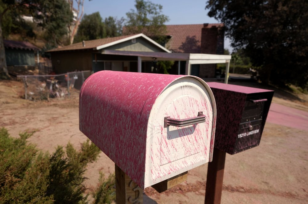 Mailboxes are covered in pink fire retardant at the Holy Fire in Lake Elsinore, California, southeast of Los Angeles, on August 11, 2018. The fire has burned 21,473 acres and was 29 percent contained as of 8:30 a.m. Saturday, according to the Cleveland National Forest.