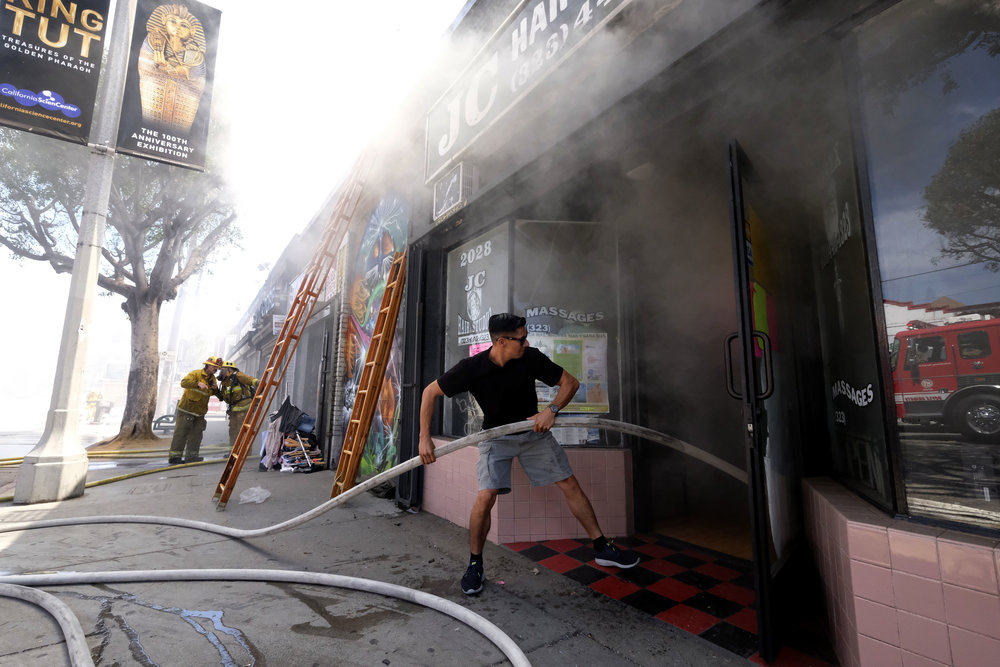 A man helps firefighters to pull a hose during a fire in a hair salon on August 30, 2018 in East Los Angeles.