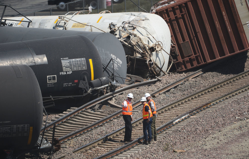 Railroad officials inspect a derailment at the base of the Cajon Pass in Devore Tuesday, August 21, 2018. Thirteen tanker cars derailed near Cajon Blvd and Devore Rd causing the evacuation of Fed Ex distribution center. A perimeter of 1,000 feet of was created by officials as a precautionary reason. Cause of the derailment of the south bound freight train is under investigation. Train traffic in the area has been suspended.