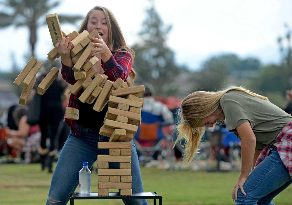 Emily Ehli, 14, reacts as her Jenga tower falls as her younger sister Ashley, 12, both from Norco, laughs during the Boots In The Park country music festival Saturday, October 6, 2018 at the BackYard at SilverLakes in Norco. Billy Currington, LOCASH and others performed at the event.