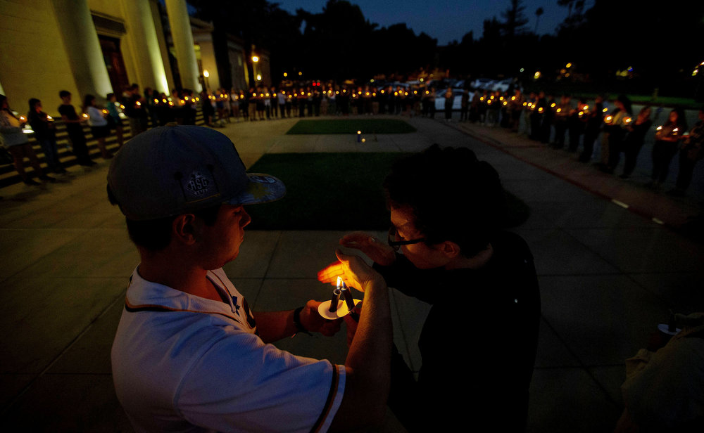 University of Redlands student Donald Johnson, rights has is candle lite by a fellow student as more than 100 people turnout to honor the 11 victims of the synagogue shooting during a candlelight vigil in front of the University of Redlands Memorial Chapel in Redlands on Tuesday, October 30, 2018.