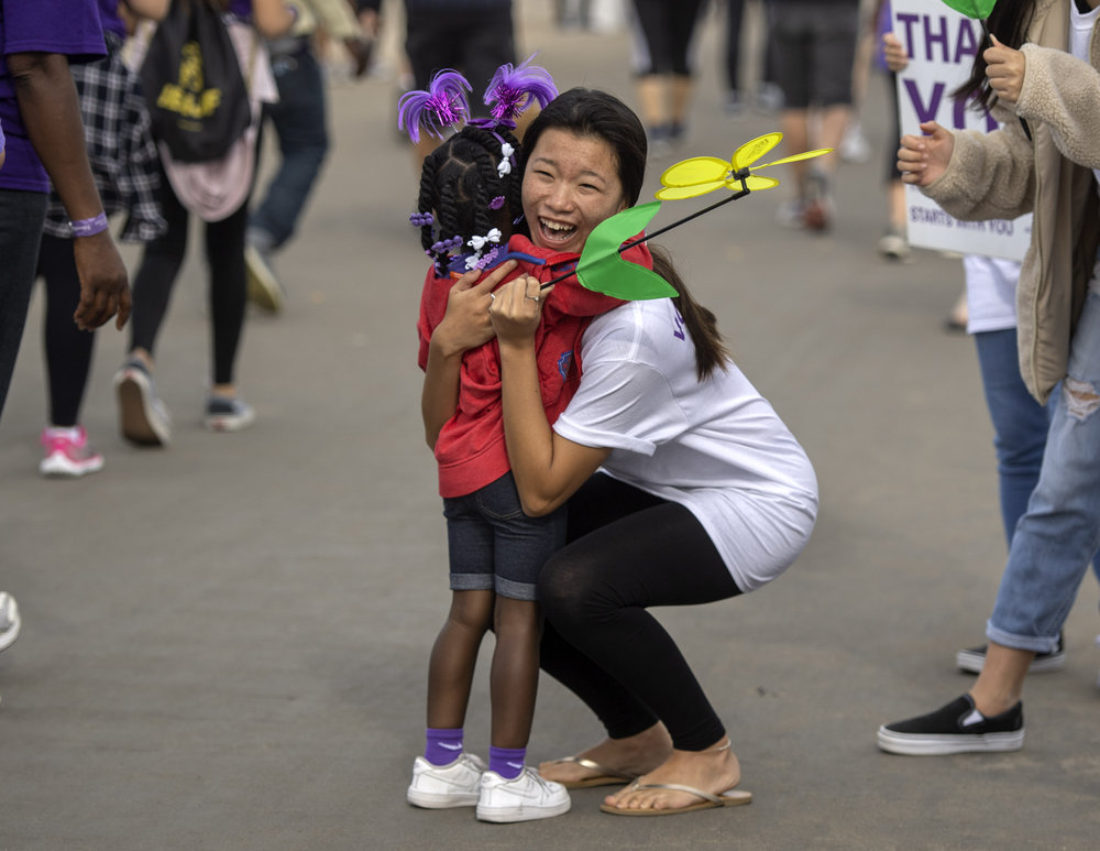 Bolsa Grande High School volunteer Ivy Pham, 16, gets a impromptu hug from 4-year-old Genesis Thomas while cheering her on during the Walk to End Alzheimer's in Huntington Beach on Saturday, October 6, 2018. (Photo by Mindy Schauer, Orange County Register/SCNG)