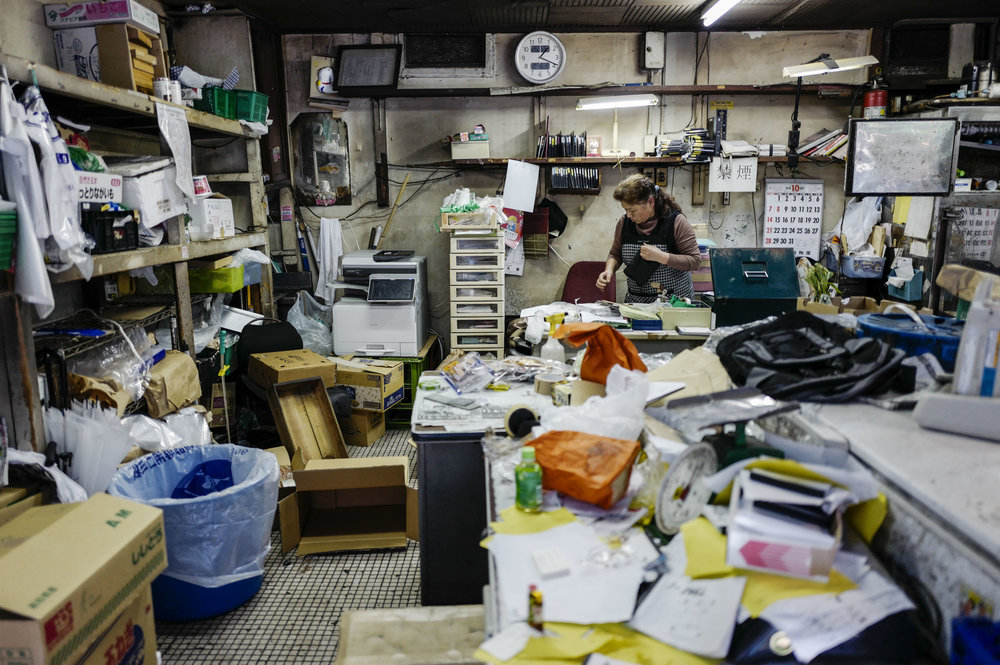 A wholeseller cleans up her store in Tsukiji fish wholesale market during its final day of operations ahead of relocation to the nearby Toyosu waterfront district, in Tokyo on Oct. 6, 2018. The world's largest fish market, which has been in operation for 83 years, is being moved as part of the redevelopment for the 2020 Olympic Games.