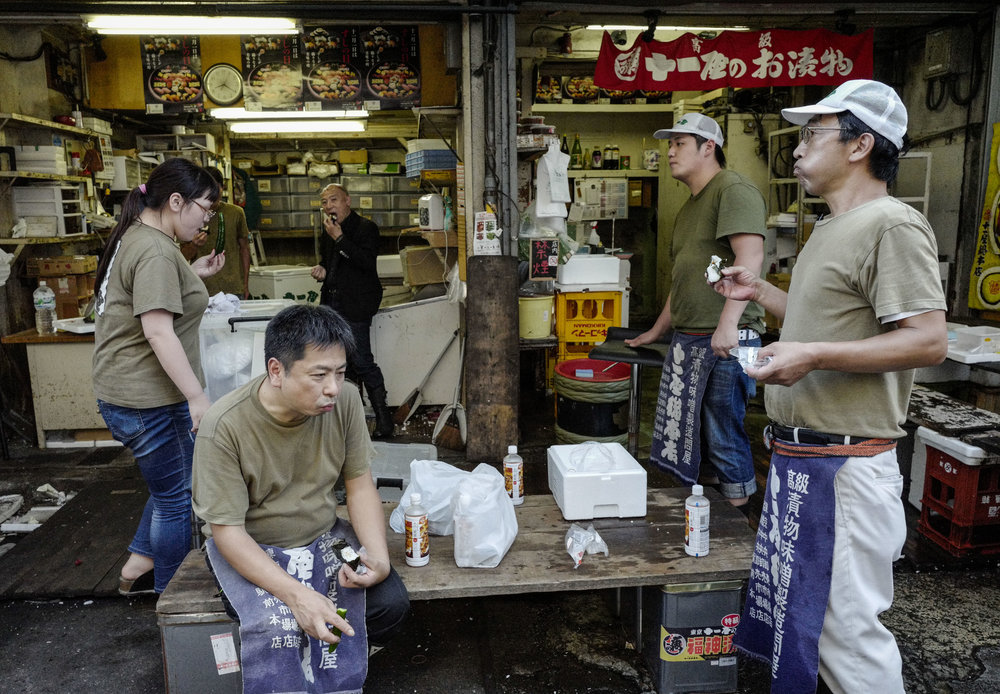 Wholesellers take break at an alley in Tsukiji fish wholesale market during its final day of operations ahead of relocation to the nearby Toyosu waterfront district, in Tokyo on Oct. 6, 2018. The world's largest fish market, which has been in operation for 83 years, is being moved as part of the redevelopment for the 2020 Olympic Games.