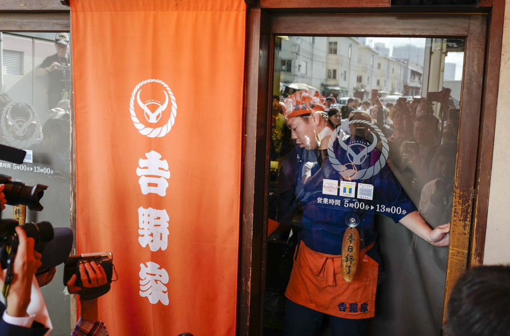 A waiter closes thier business door in Tsukiji fish wholesale market during its final day of operations ahead of relocation to the nearby Toyosu waterfront district, in Tokyo on Oct. 6, 2018. The world's largest fish market, which has been in operation for 83 years, is being moved as part of the redevelopment for the 2020 Olympic Games.
