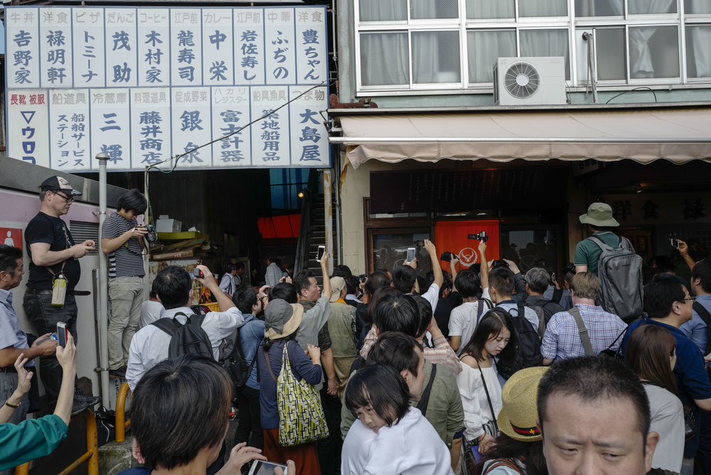 People crowd at a storefront in Tsukiji fish wholesale market during its final day of operations ahead of relocation to the nearby Toyosu waterfront district, in Tokyo on Oct. 6, 2018. The world's largest fish market, which has been in operation for 83 years, is being moved as part of the redevelopment for the 2020 Olympic Games.