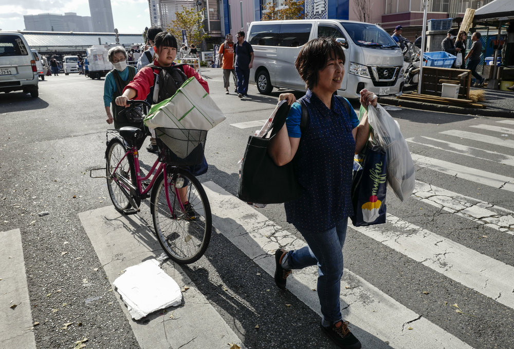 Wholesellers leave the Tsukiji fish wholesale market during its final day of operations ahead of relocation to the nearby Toyosu waterfront district, in Tokyo on Oct. 6, 2018. The world's largest fish market, which has been in operation for 83 years, is being moved as part of the redevelopment for the 2020 Olympic Games.