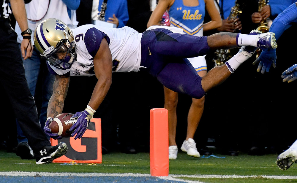Running back Myles Gaskin #9 of the Washington Huskies dives for the touchdown, but the play was called back after replay in the first half of a NCAA football game against the UCLA Bruins at the Rose Bowl on Saturday, October 6, 2018 in Pasadena, California.