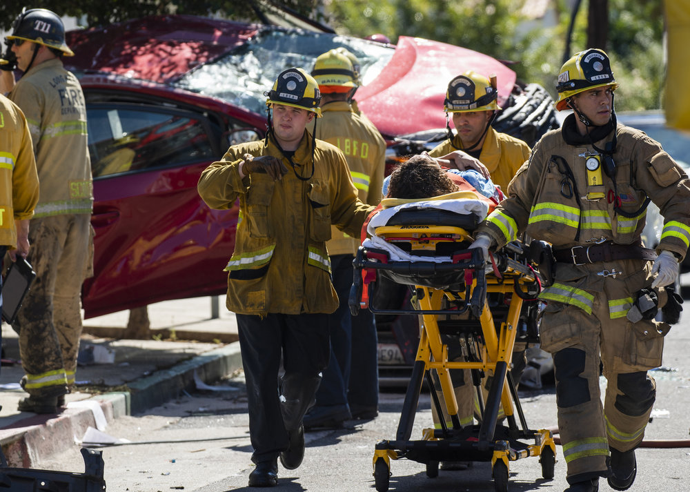 Long Beach firefighters take the last of three injured people who were hospitalized after a crash that smashed a fire hydrant and ended with one car at least partially on top of another at the 1100 block E Wardlow in Long Beach October 16, 2018.