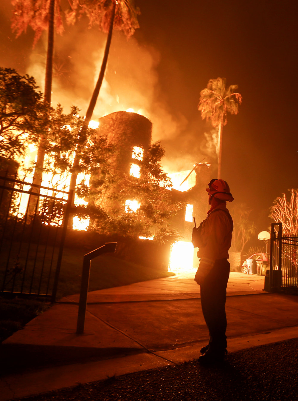 A firefighter keeps watch the Woolsey fire burning a home in Malibu, Calif., Friday, Nov. 9, 2018.