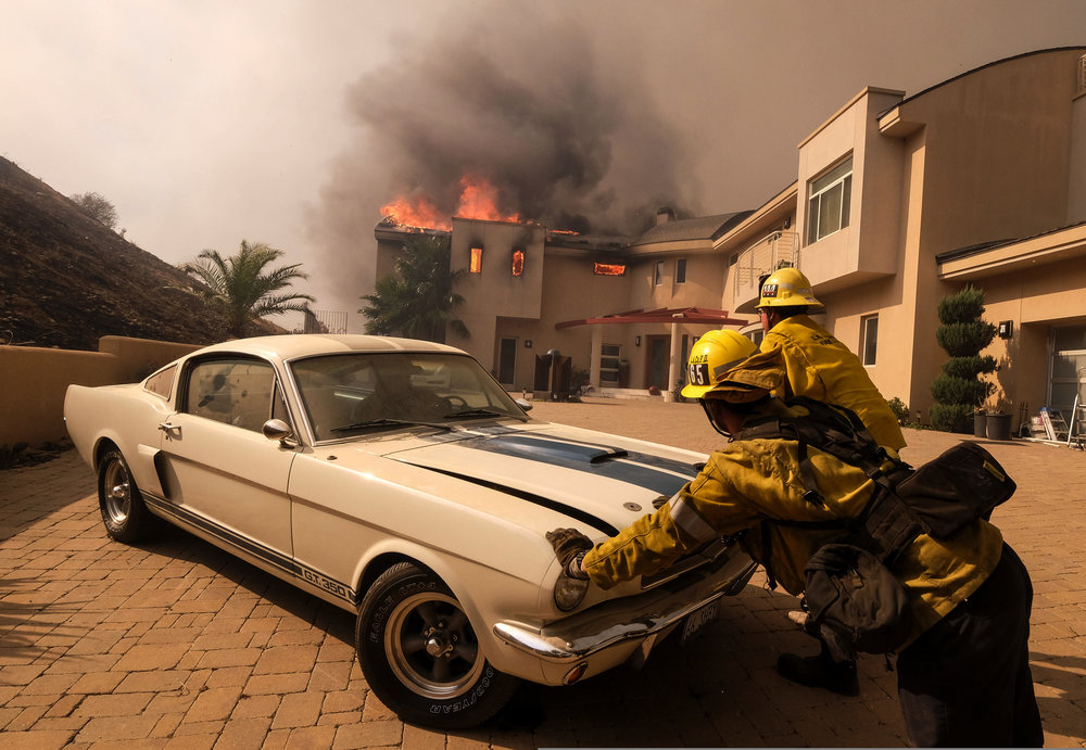 Firefighters push a vehicle from a garage as the Woolsey fire burning a home near Malibu Lake in Malibu, Calif., Friday, Nov. 9, 2018.