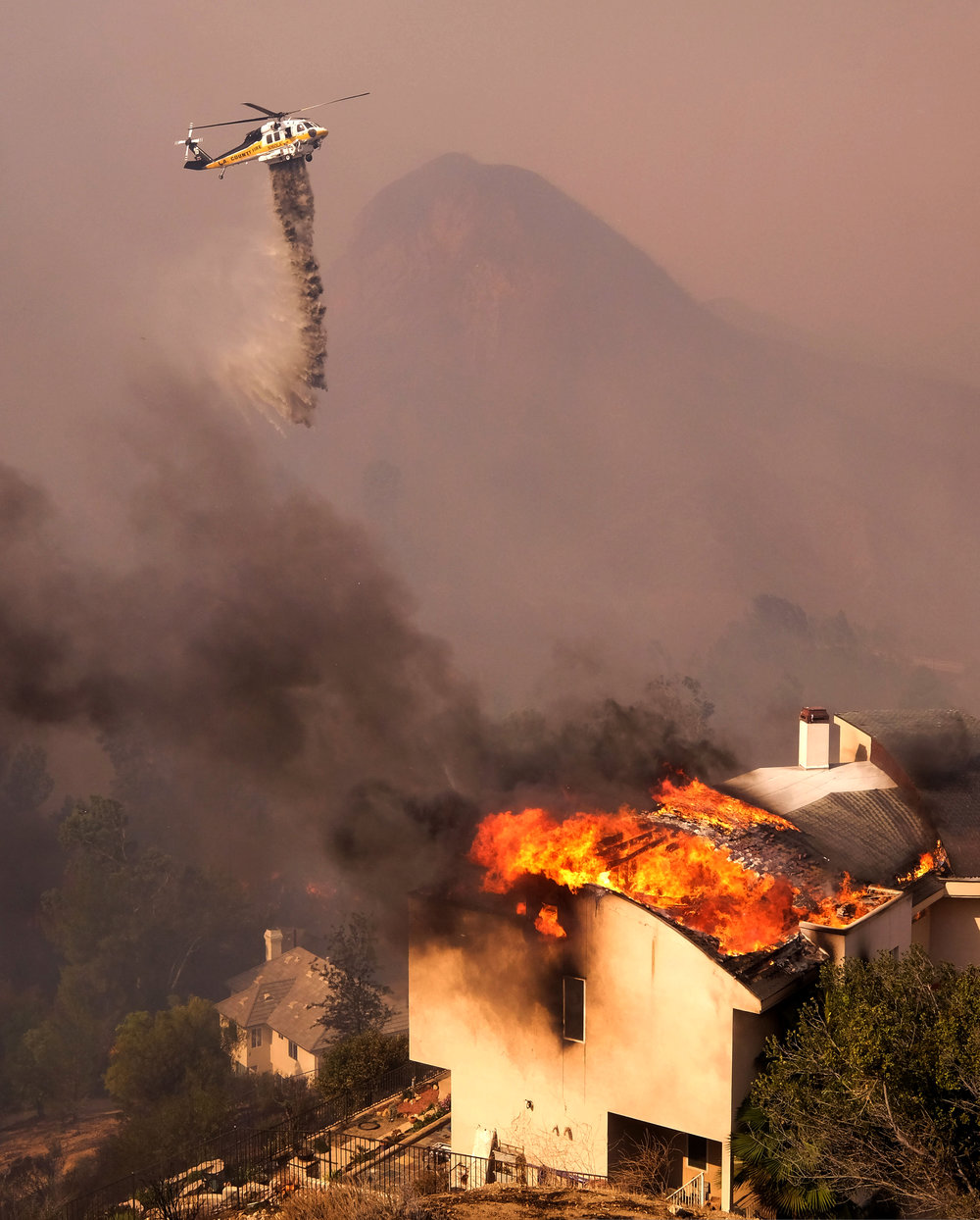 A helicopter drops water while the Woolsey fire burning a home near Malibu Lake in Malibu, Calif., Friday, Nov. 9, 2018.