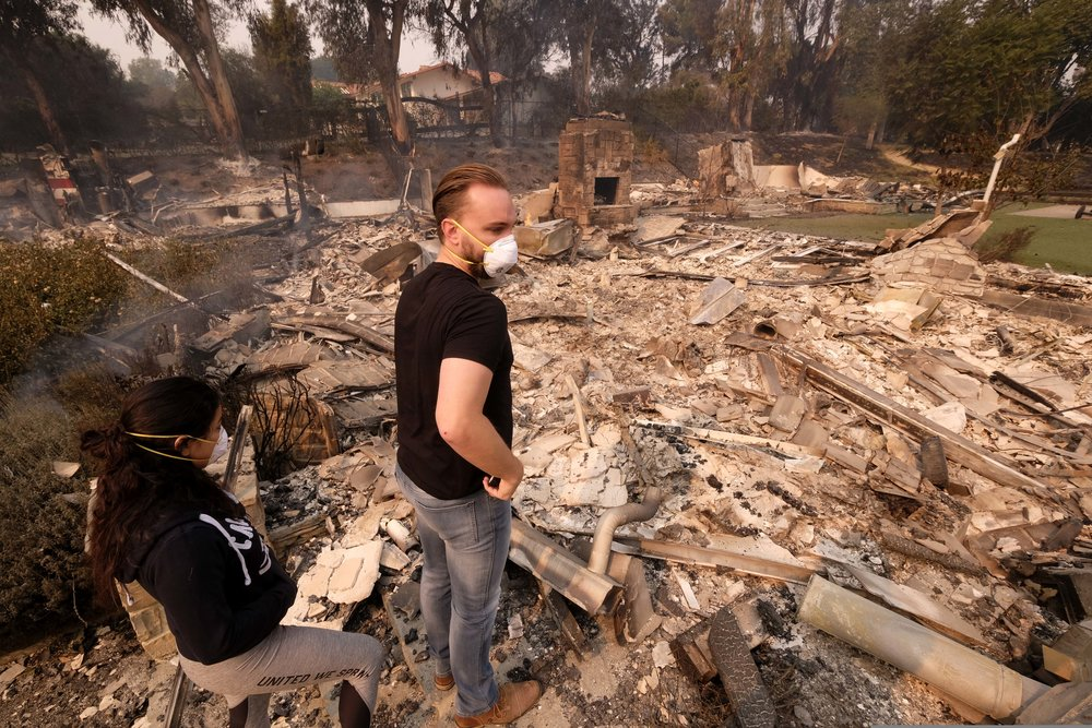 Alexander Tobolsky, right, and his girl friend Dina Arias, return to his home where burned out by the fire in Malibu, Calif., Friday, Nov. 10, 2018.