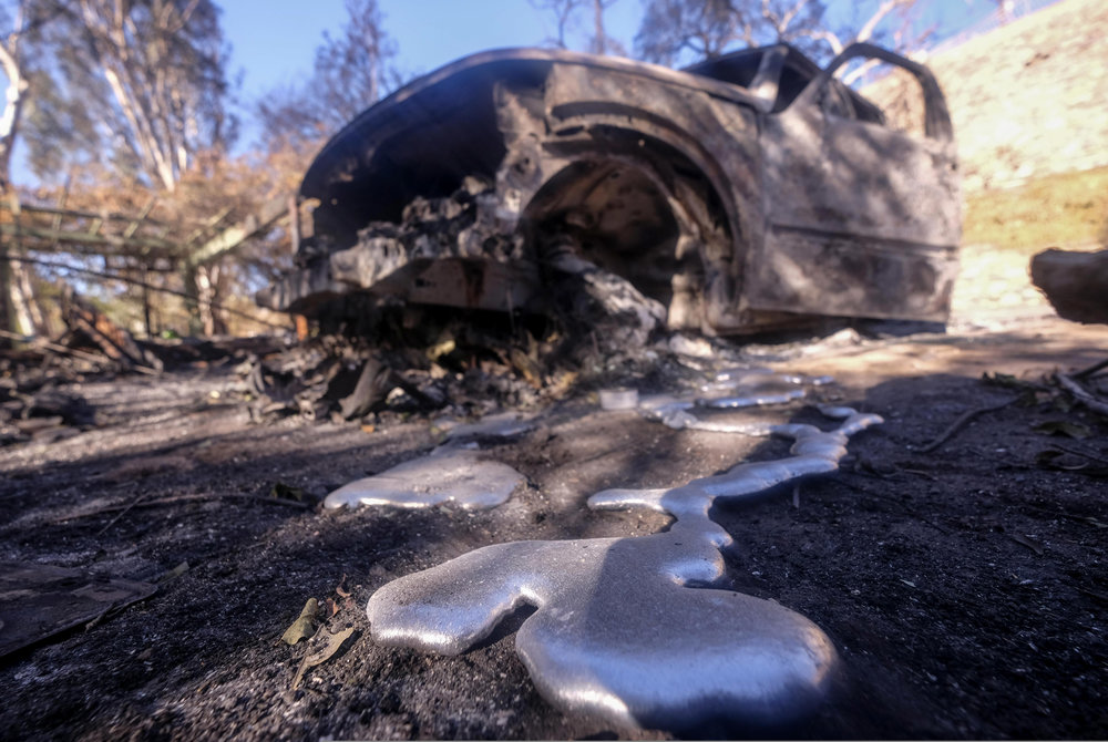 The burned vehicles are seen at a home destroyed by wildfire in Malibu, California, on November 14, 2018.
