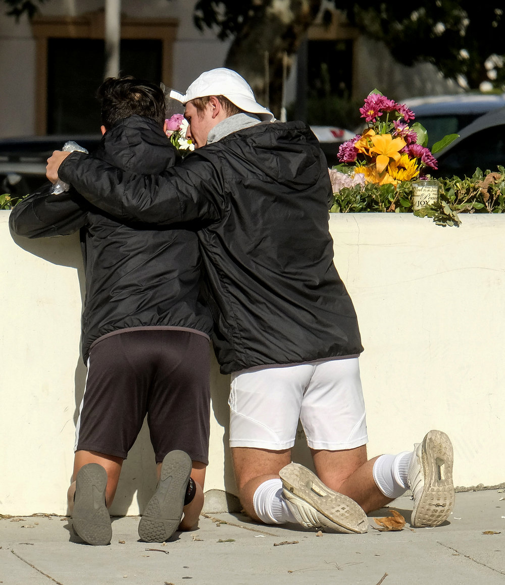 People place flowers near the scene Thursday, Nov. 8, 2018, in Thousand Oaks, Calif. after a gunman opened fire Wednesday evening inside a country music bar, killing multiple people including a Sheriff officer.