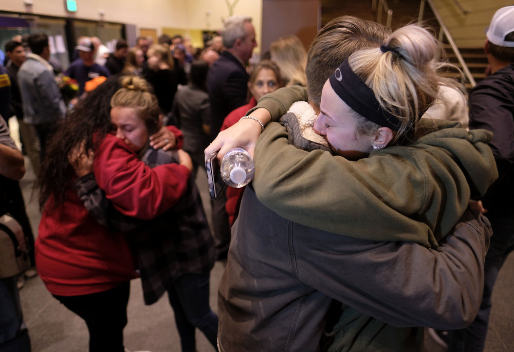 People comfort each other gather after a candlelight vigil for the victims of the mass shooting in Thousand Oaks , Calif., Thursday, Nov. 8, 2018. A gunman opened fire Wednesday evening inside a country music bar, killing multiple people including a Sheriff officer.