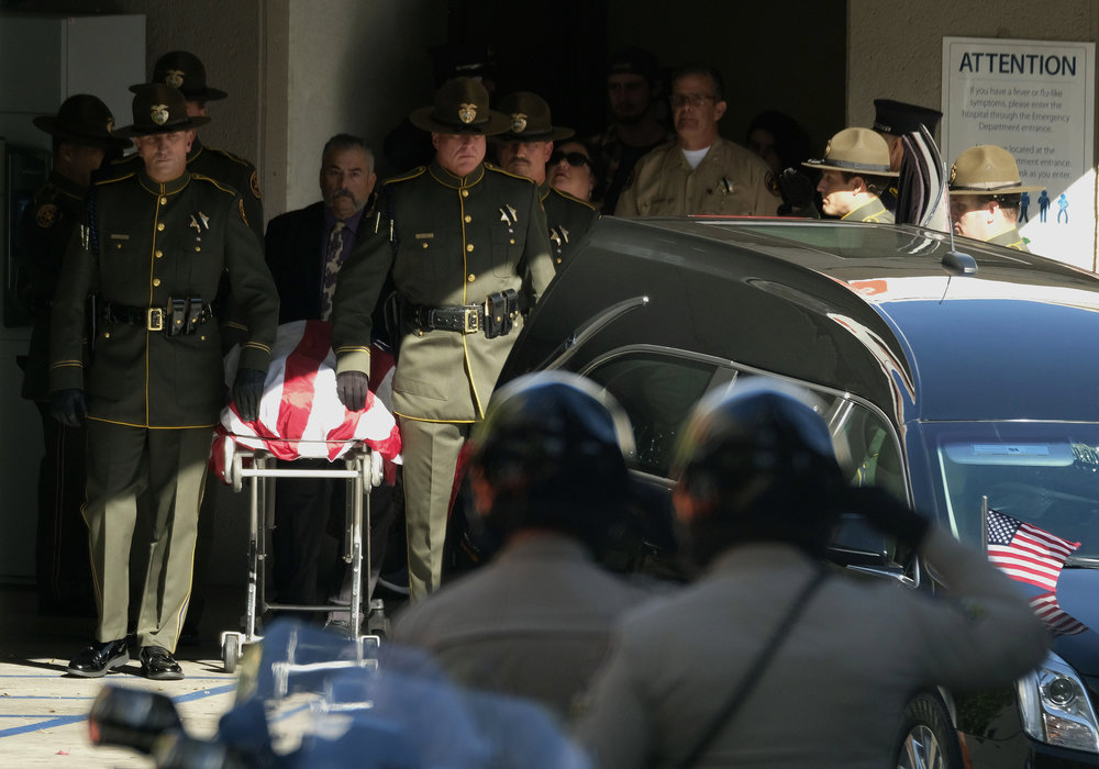 The body of Ventura County Sheriff Sgt. Ron Helus, who was shot and killed in a mass shooting at a bar is transferred to a hearse for procession from the Los Robles Medical Center in Thousand Oaks, California, U.S. November 8, 2018.