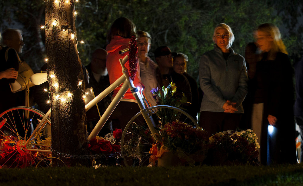 Betsy Hipple, second from right,  life partner of Leslie Pray, 54, who was killed Saturday while riding her bike along Mills Avenue near Radcliffe Drive, looks over the ghost bike during a candle light vigil to honor Pray in Claremont on Monday, November 5, 2018.