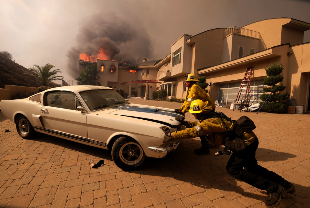 Firefighters push a vehicle from a garage as the Woolsy fire burning a home near Malibu Lake in Malibu, Calif., Friday, Nov. 9, 2018.