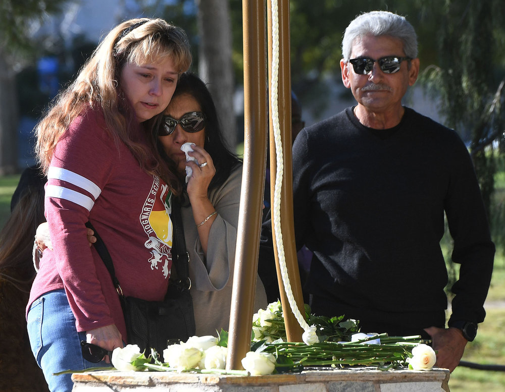 Robert Velasco (right), whose daughter Yvette was killed in the Inland Regional Center mass shooting, stands next to a memorial on the Cal State San Bernardino campus as his wife Mari (center) hugs one of Yvette's coworkers and survivors (left), who wished not to be identified, during a memorial gathering Sunday December 2, 2018 in the Peace Garden at Cal State San Bernardino marking the third anniversary of the mass shooting at the Inland Regional Center in San Bernardino where 14 were killed and 22 injured in San Bernardino.