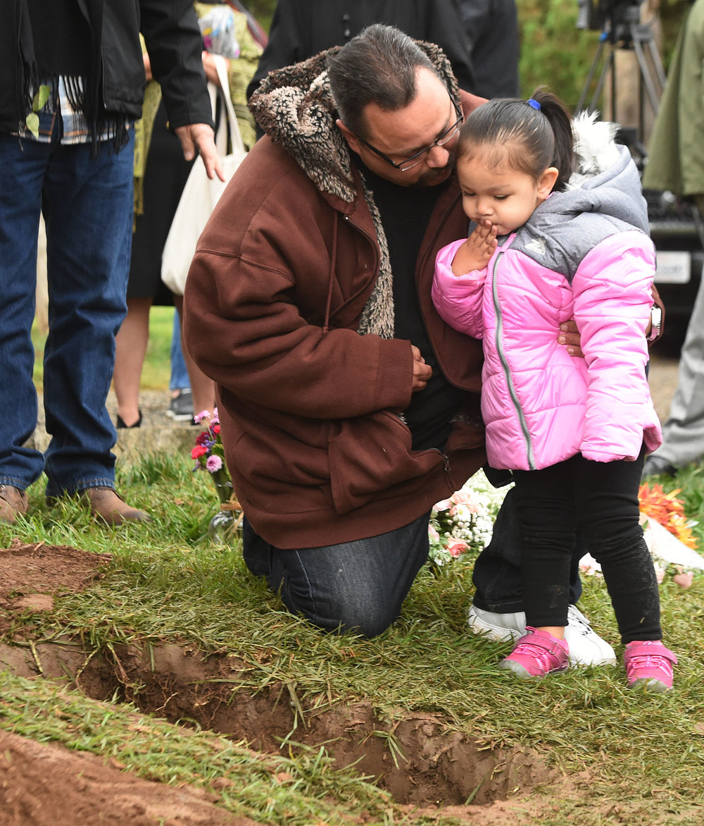Robert West supports his daughter Sophia, 2, as she blows a kiss towards the small casket containing the remains of Baby Jane Doe at Sunnyslope Cemetery in Corona, Thursday, December 6, 2018, West's infant son is buried only feet away. The newborn infant was found in a cardboard box near the 15 freeway in Corona in July. Corona police and fire departments along with others contributed to make the funeral possible for the child. Police are still searching for the person or persons responsible.