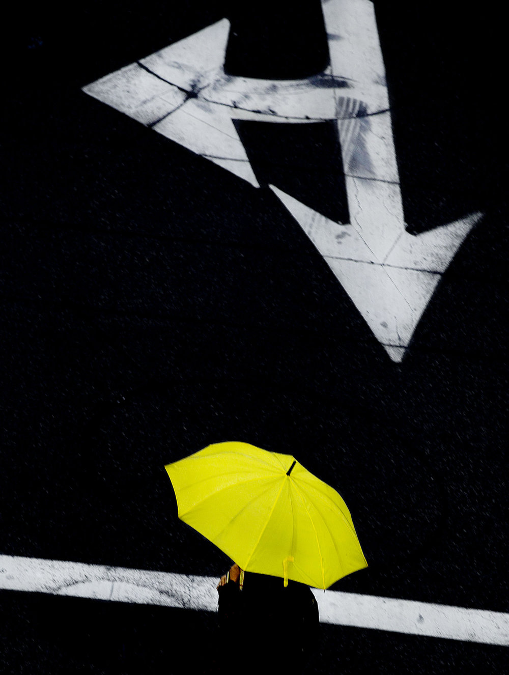 A woman uses an bright yellow umbrella to keep the rain off her as she crosses Orange Street during a winter rain shower in Riverside on Thursday, December 6, 2018.