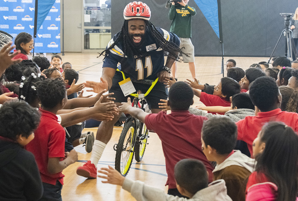 Los Angeles Charger Geremy Davis high-five students as the team donates 150 bikes to 2nd and 3rd-grade students who took part in an essay competition. The bikes were purchased by the team and California Resources Company at Cesar Chavez Elementary School in Long Beach December 4, 2018.