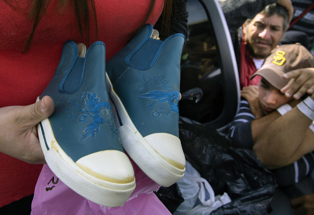 A Tijuana church group provides new shoes and clothing to Central American migrants outside the El Barretal shelter on Tuesday, December 4, 2018.