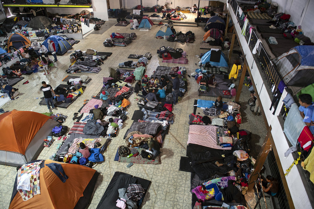 Hundreds of migrants are taking shelter at El Barretal in Tijuana. The inside is dark and features three stories of space with no running water.