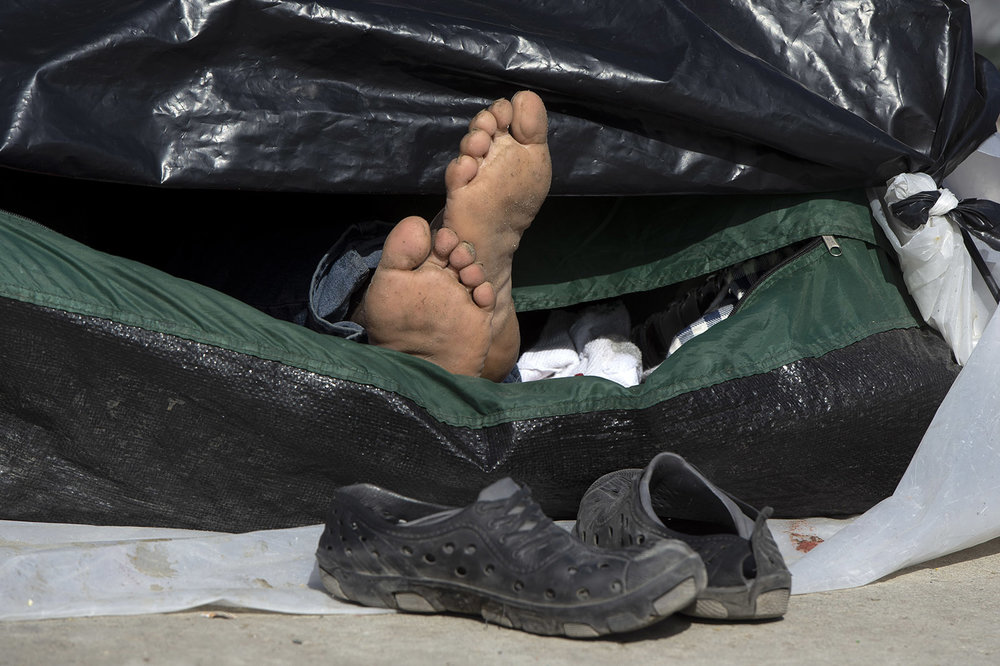 A man suns his feet as he sleeps outside the El Barretal shelter in Tijuana on Tuesday, December 4, 2018. Shoes are one of the most needed items to caravan walkers who wore them out on the trek to Mexico.