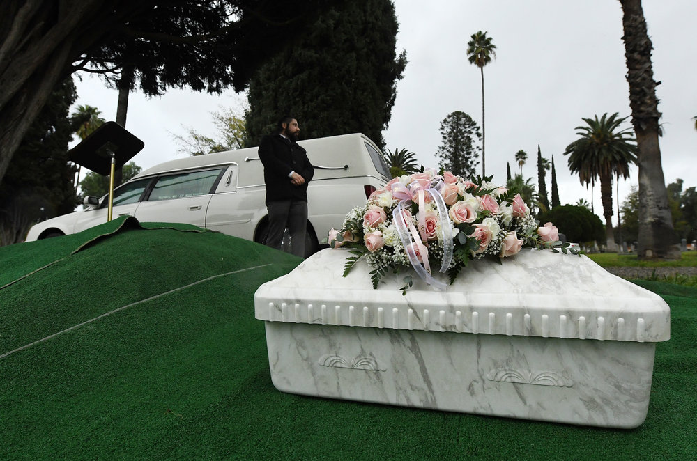 Paul Mariscal, with Thomas Miller Mortuary, stands watch over the casket of Baby Jane Doe prior to her burial at Sunnyslope Cemetery in Corona, Thursday, December 6, 2018. The newborn infant was found in a cardboard box near the 15 freeway in Corona in July. Corona police and fire departments along with others contributed to make the funeral possible for the child. Police are still searching for the person or persons responsible.