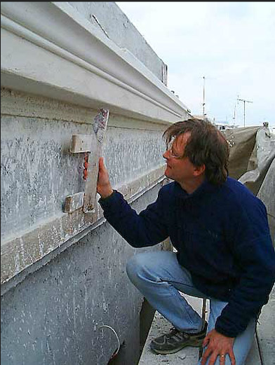 John holds the template that the mason uses to sculpt the cornice