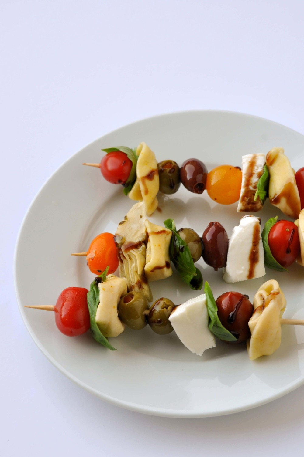 Antipasto Skewers - a quick, easy, & vegetarian dinner made from cheese tortellini, olives, cherries, mozzarella, and artichokes.