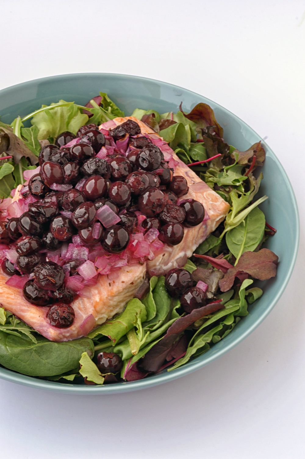 Salmon with blueberries and white wine on a bed of mixed greens. A healthy lunch or dinner recipe. | Shiny Happy Bright
