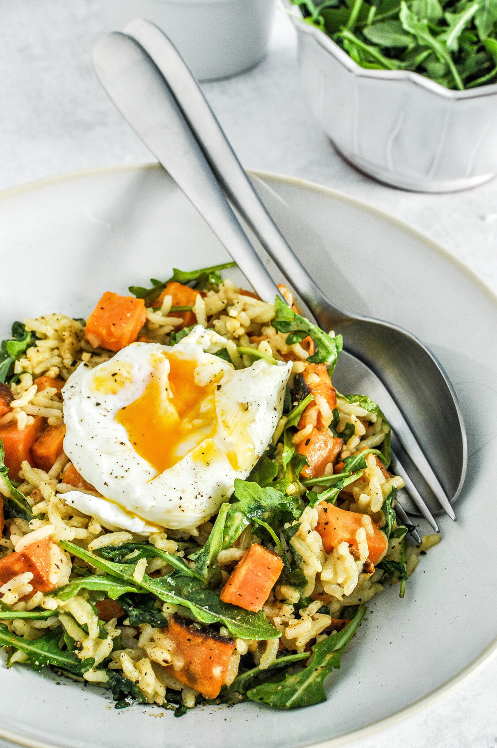 Sweet Potato Green Curry Bowl. This rice bowl with sweet potatoes, green curry, arugula, and a poached egg is a delicious brunch or lunch.