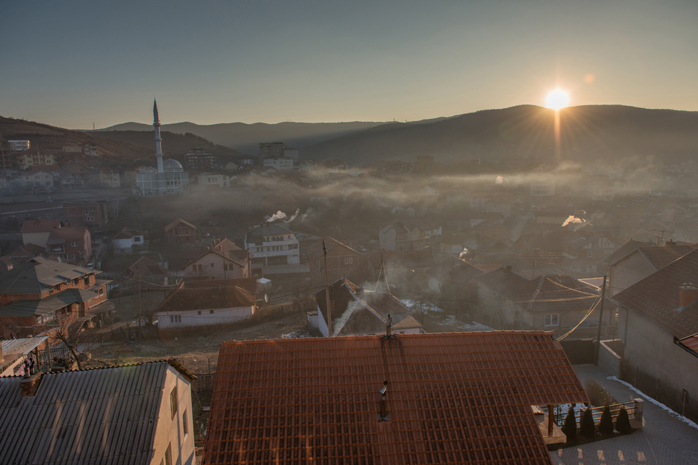 Smog from two brown cole plants pulls through Pristina in the early morning