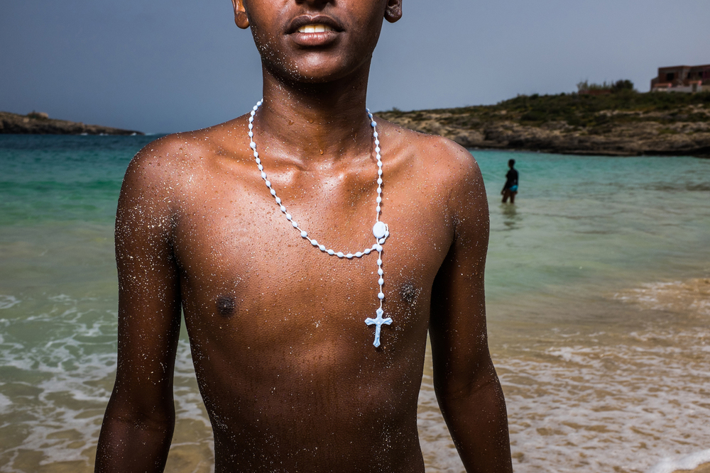 Eritrean Refugee who took the treacherous  journey across the Mediteranean two weeks ago, goes for a swim with his friends.