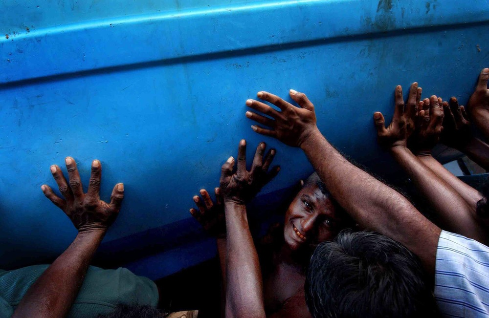 Fishermen and shipyard workers try to stabilize a boat damaged by the Tsunami