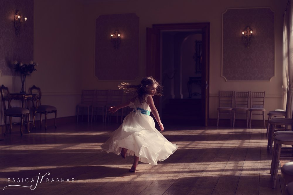 "This is one of my favourite images. It was during the wedding breakfast so I had put my camera down & was resting my legs. Then I noticed the incredible light coming through the windows in this room next to me. I went slightly frantic, picked up my camera & stood in there overwhelmed thinking ""I need an image, I need an image"" but I didn't want to pull anyone away from their meal. Then a mini miracle happened as the bride & groom's daughter ran into the room. So I just asked her if she would like to spin for me & show me her pretty dress. Then this happened. This is a great example of a natural but refined moment."