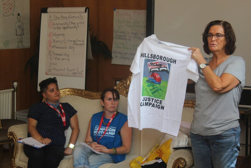 Image Description: Sheila Coleman who worked on the Hillsborough campaign speaks at Bootcamp, she holds up a Hillsborough Justice T-shirt with an image that describes the Sun as scum on it