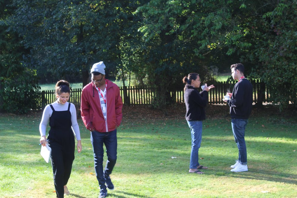 Image Description: Kimani walks in the garden with Holly, with Tom and Abi chat in the background.